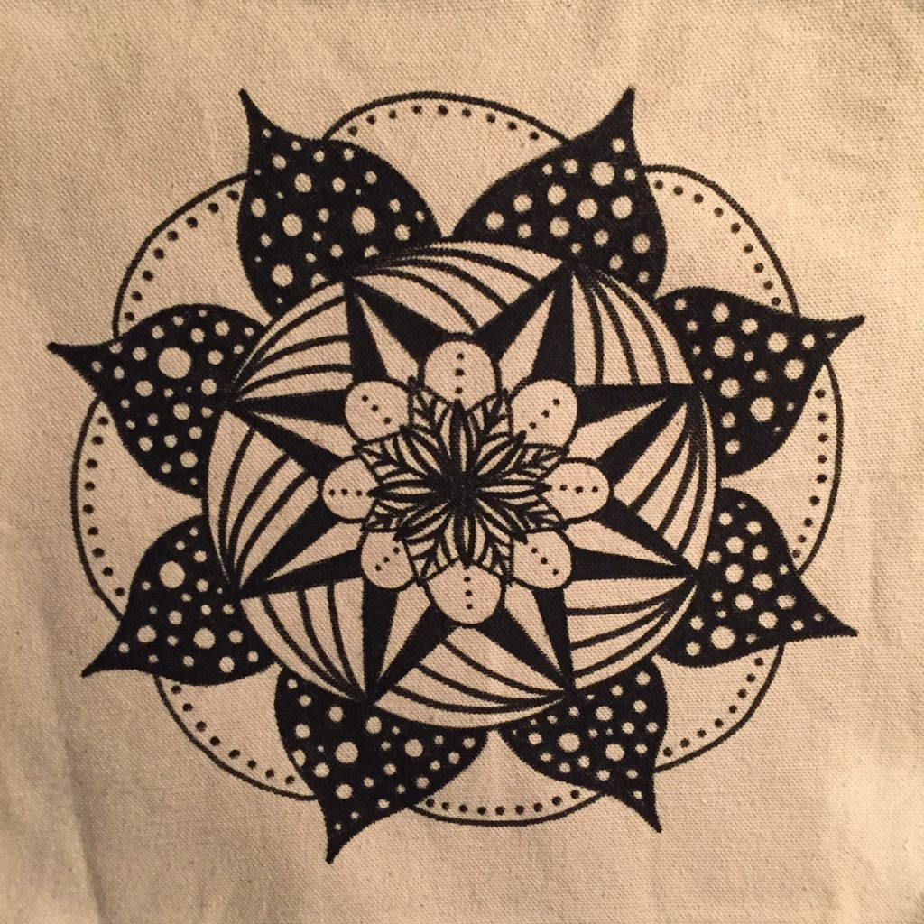 hand drawn black and white polka dot mandala on a cream colored tote bag