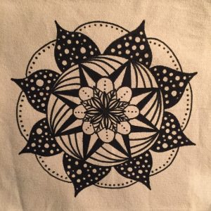 hand drawn black and white polka dot mandala on a cream colored tote bag