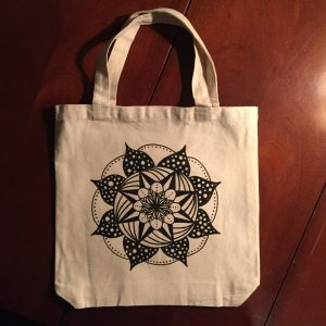 Hand drawn black and white polka dot mandala on a cream colored canvas tote bag