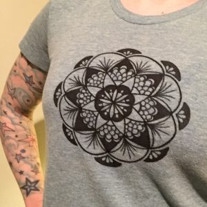 Hand drawn black fan mandala on a teal shirt in full view