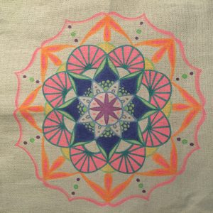 hand drawn tropical mandala in pink, blue green and orange on a grey tote bag