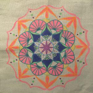 hand drawn tropical mandala in pink, blue green and orange on a grey tote bag