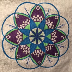 Hand drawn budding flower mandala in green, blue and purple on a white tote bag
