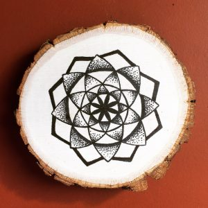 black ink star mandala on wood